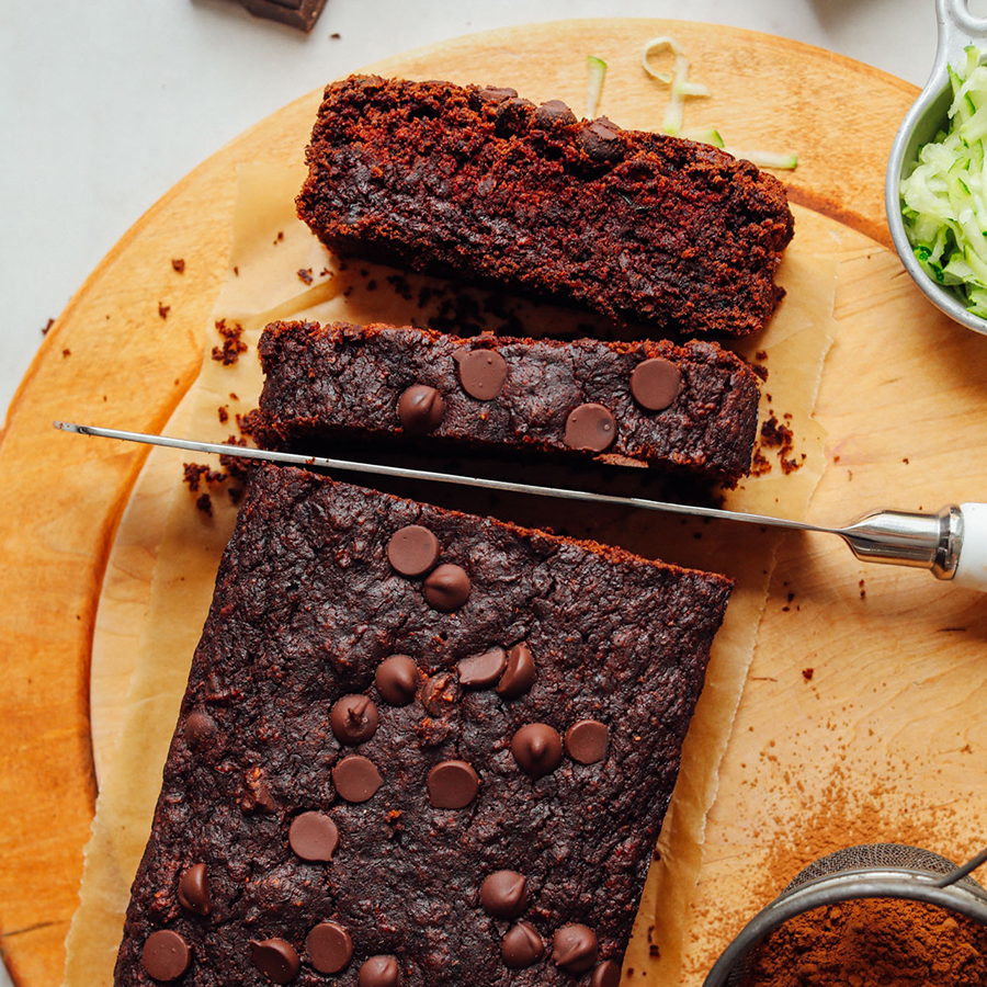 Using a knife to slice up a loaf of our amazing Vegan Chocolate Chip Zucchini Bread