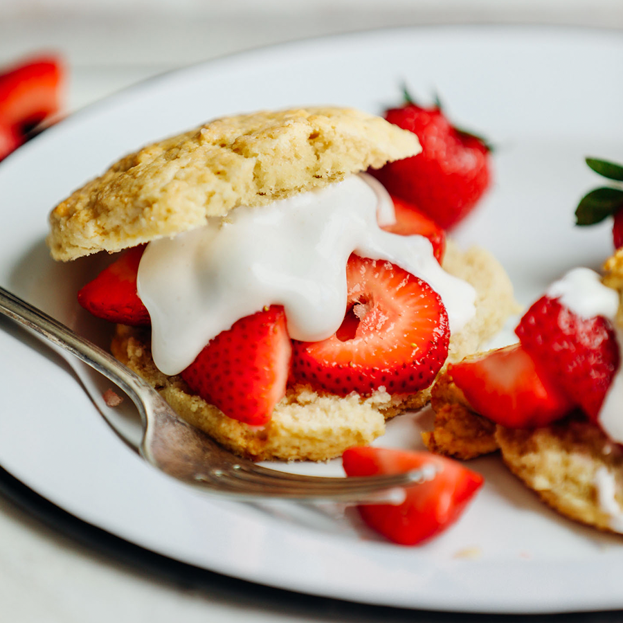 Plate with a sliced open GF Vegan Shortcake Biscuit with sliced strawberries and vegan whipped cream