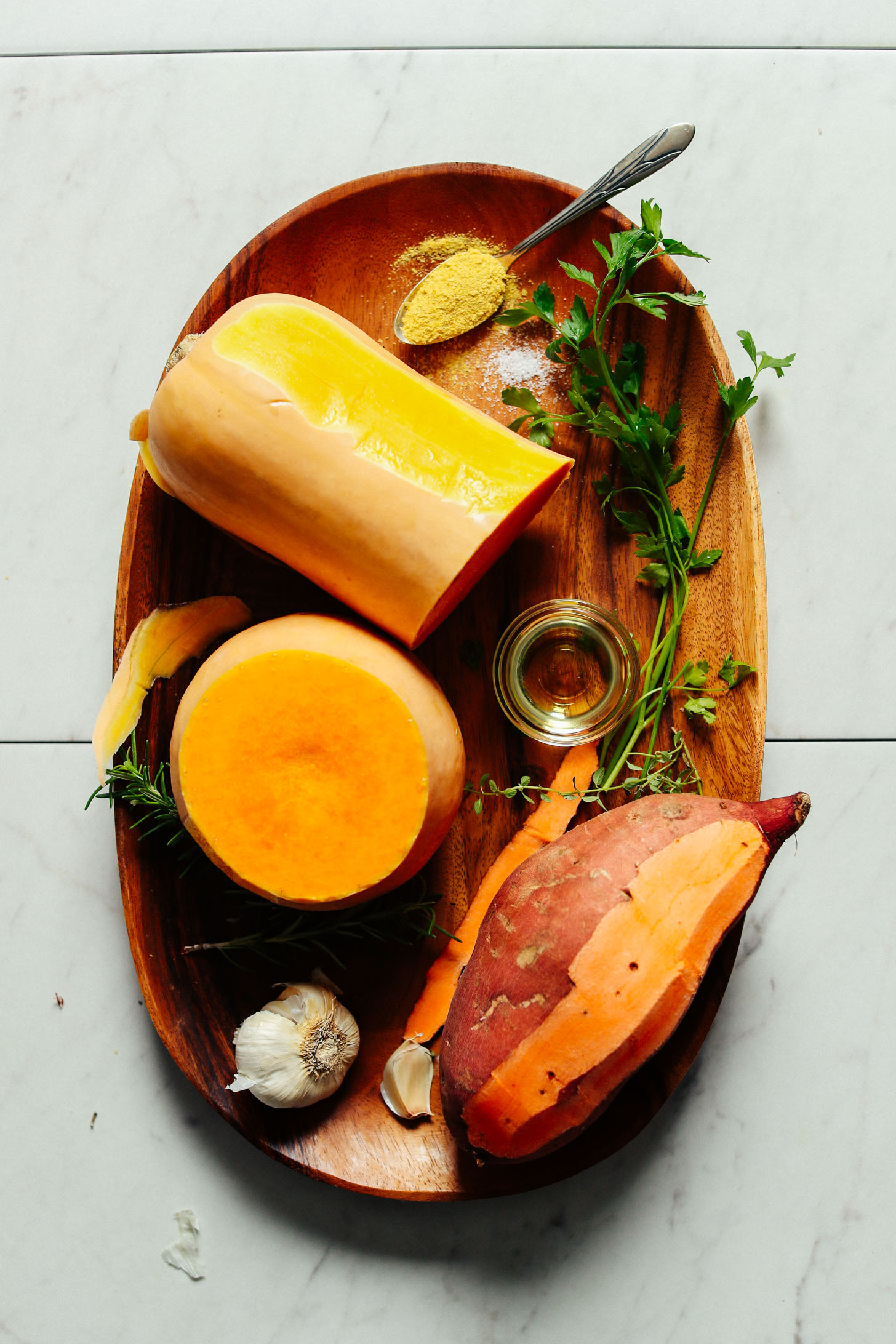 Butternut squash, sweet potato, garlic, olive oil, parsley and nutritional yeast displayed on a wooden platter