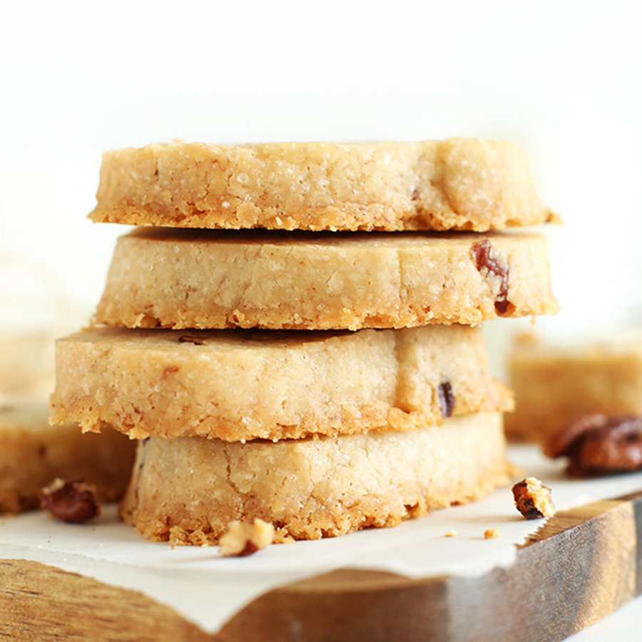 Stack of Vegan Banana Pecan Shortbread Cookies on a parchment-lined cutting board