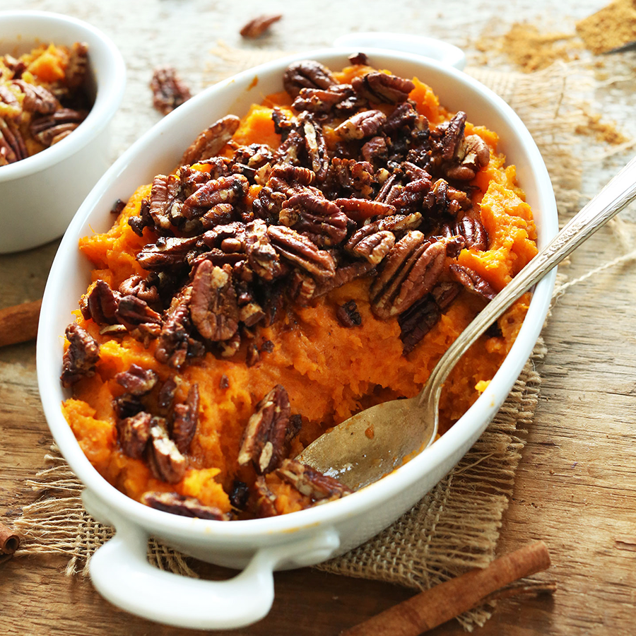 Oval-shaped white ceramic dish filled with our Butternut Squash Sweet Potato Casserole recipe topped with pecans