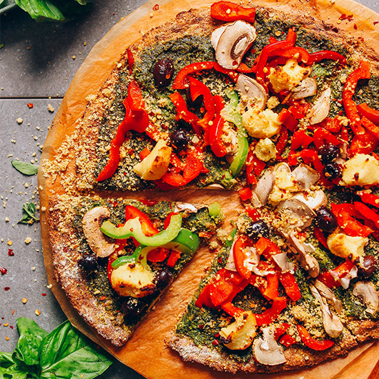Cutting board with a pizza made using our Vegan Cauliflower Pizza Crust recipe