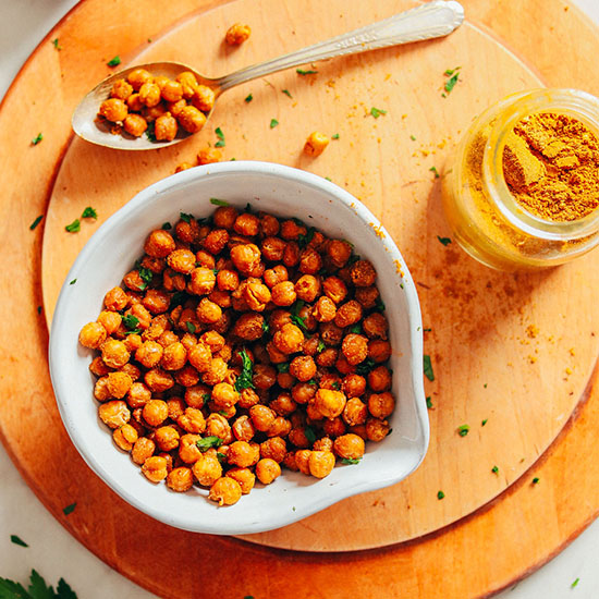 Bowl of Crispy Chickpeas on a wood cutting board with a jar of curry powder
