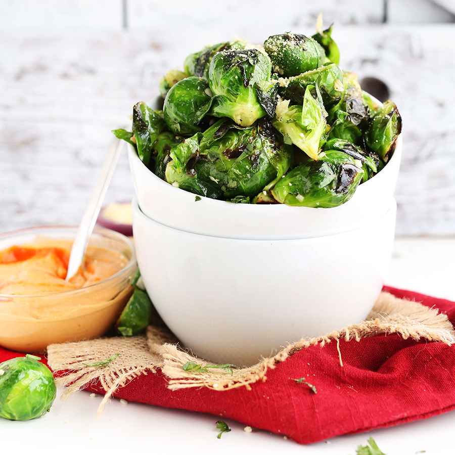 Stack of bowls holding Crispy Roasted Brussels Sprouts alongside a bowl of Vegan Sriracha Aioli