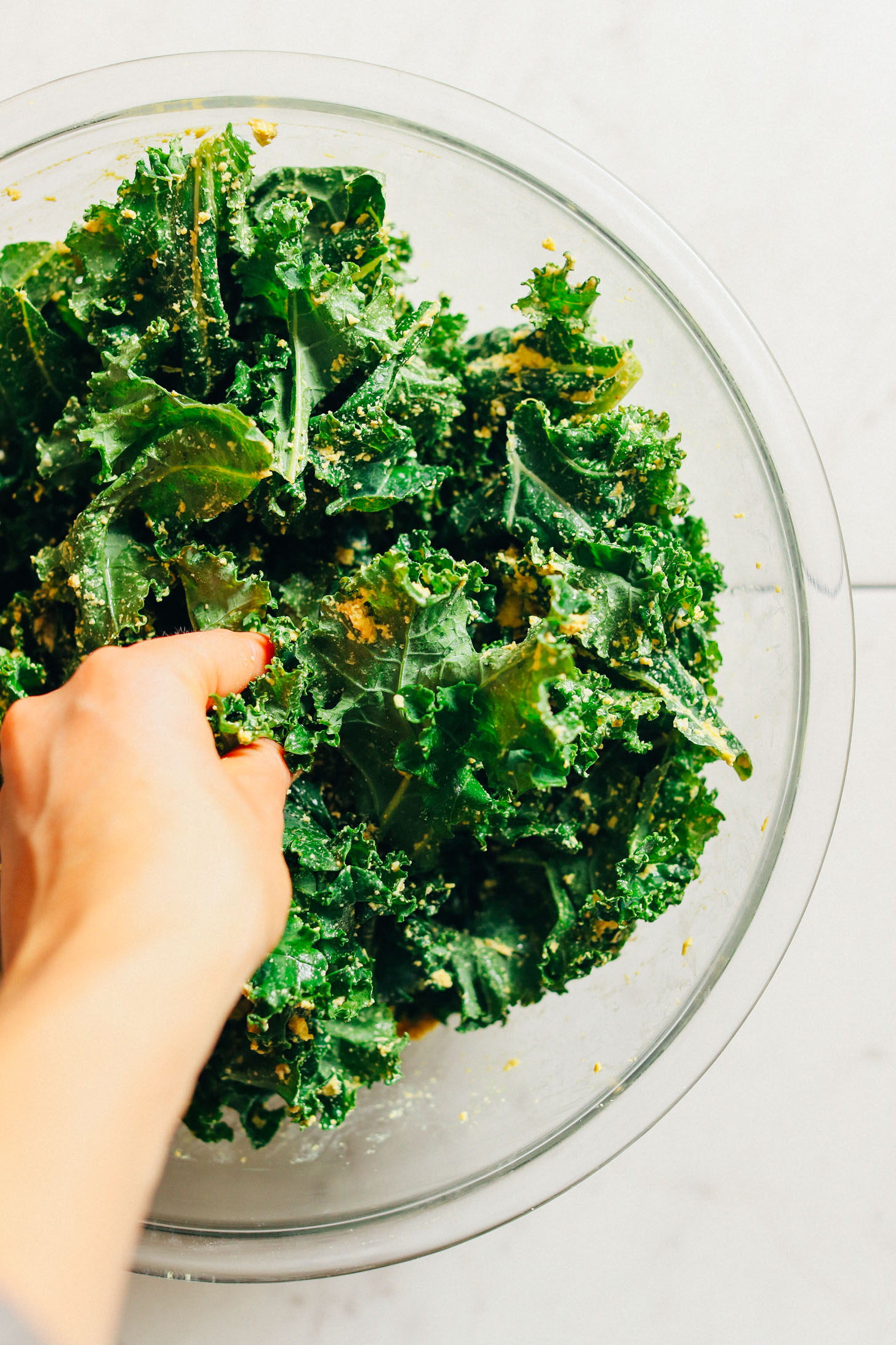 Using hands to toss kale leaves evenly with Sunflower Seed Cheeze
