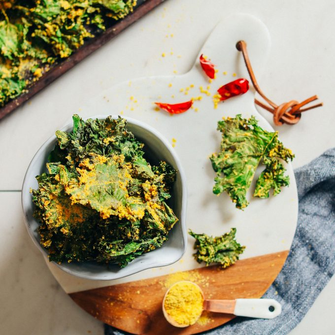 Marble cutting board with a bowl full of Crispy Baked Kale Chips coated with Sunflower Seed Cheeze