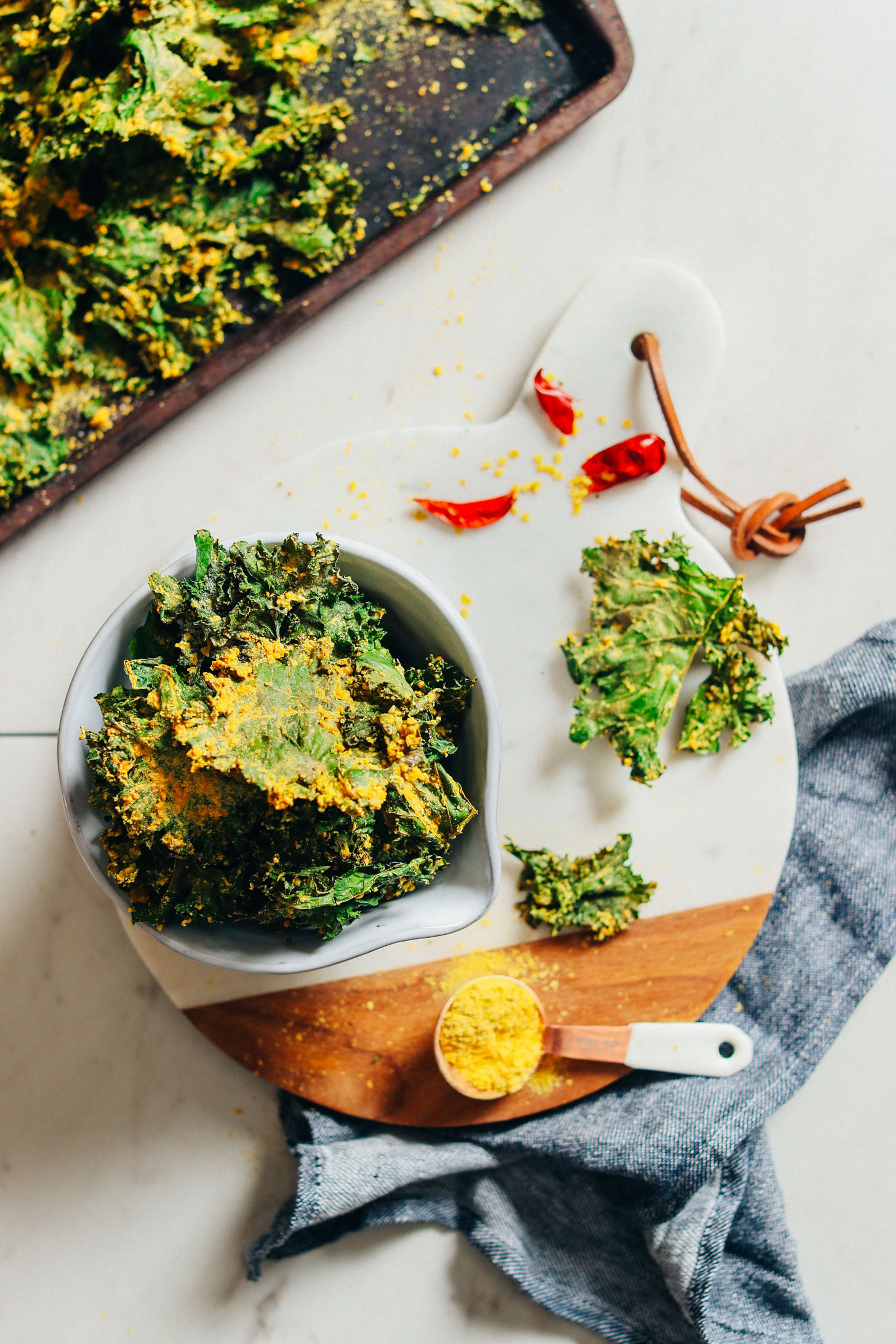 Marble cutting board with a bowl of Crispy Baked Kale Chips coated with Sunflower Seed Cheeze