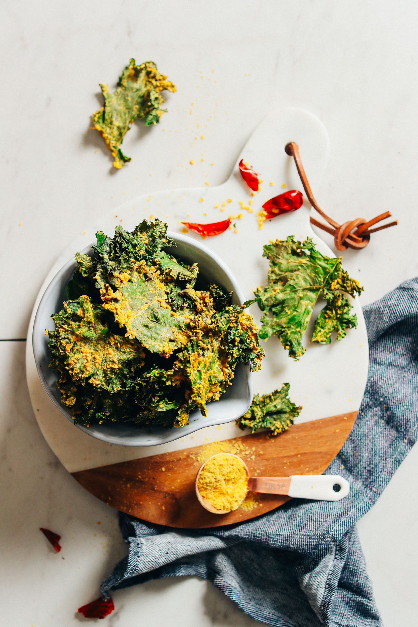 Marble cutting board with a bowl full of Crispy Baked Kale Chips for the perfect plant-based snack