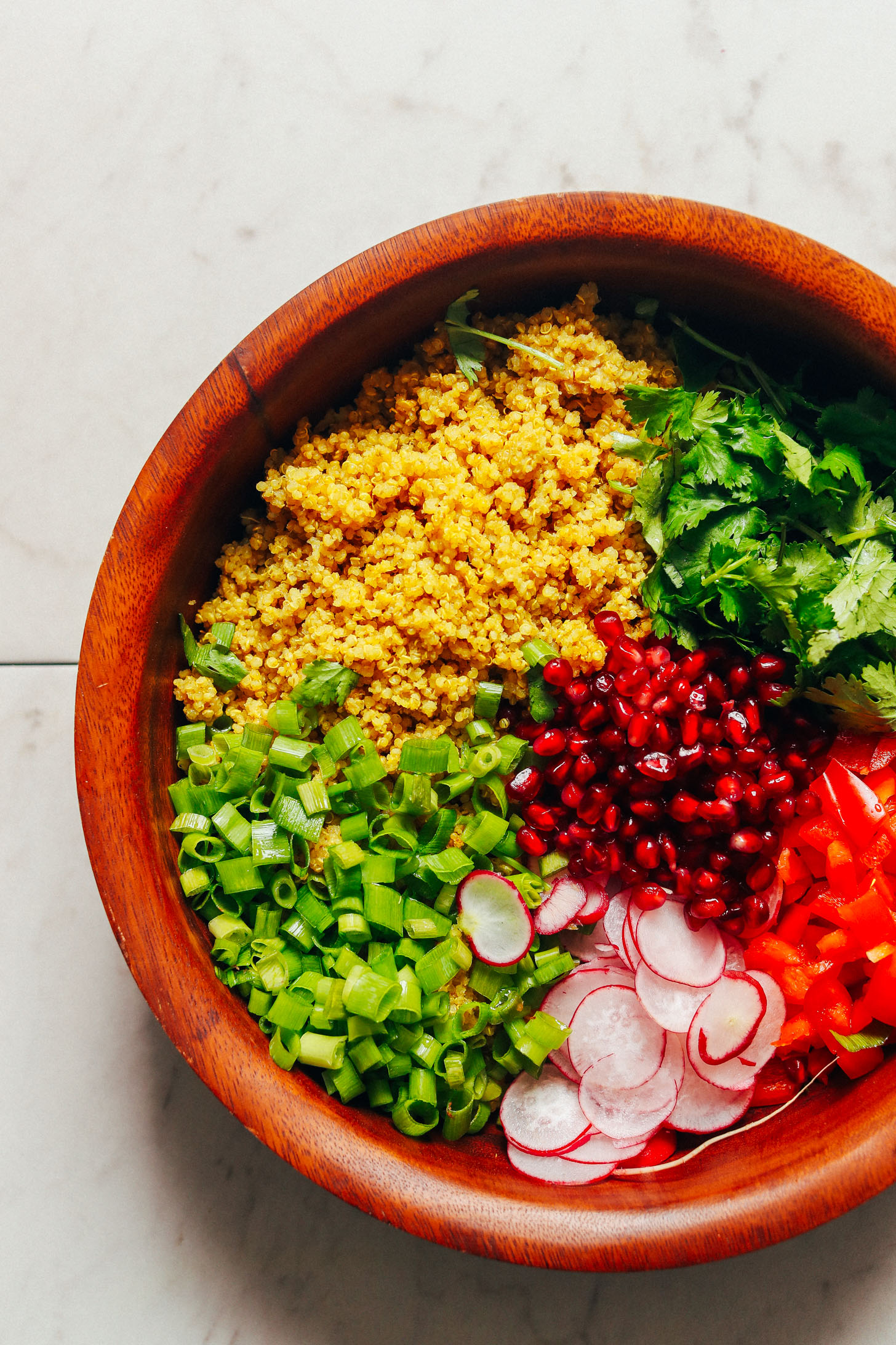 Large wooden salad bowl with Curried Quinoa Salad with vegetables