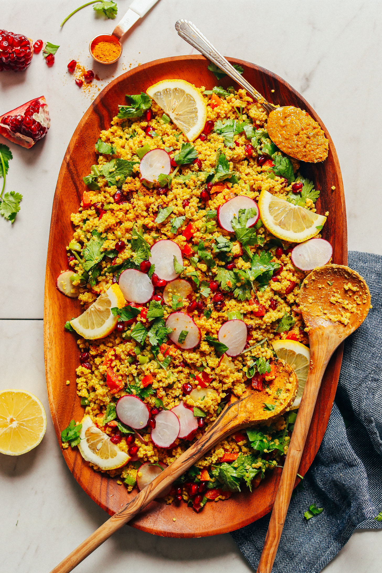 Large wood platter with Curried Quinoa Salad served with fresh vegetables and lemon slices