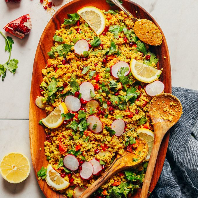 Large wood platter with gluten-free vegan Curried Quinoa Salad with fresh vegetables