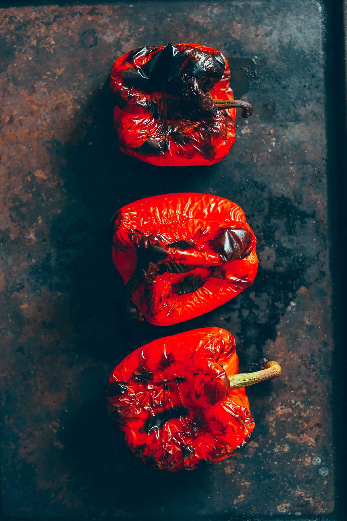 Charred red bell peppers on a baking sheet ready for making Muhamarra Dip