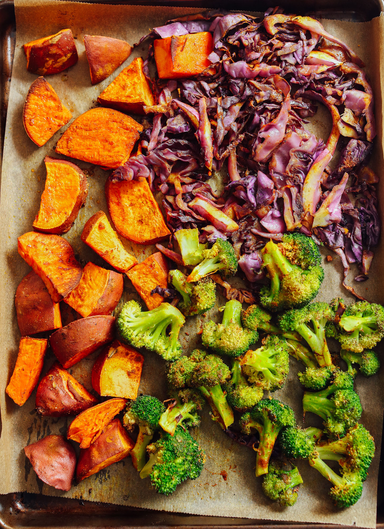 Freshly roasted sweet potatoes, broccoli, and cabbage on a parchment-lined baking sheet