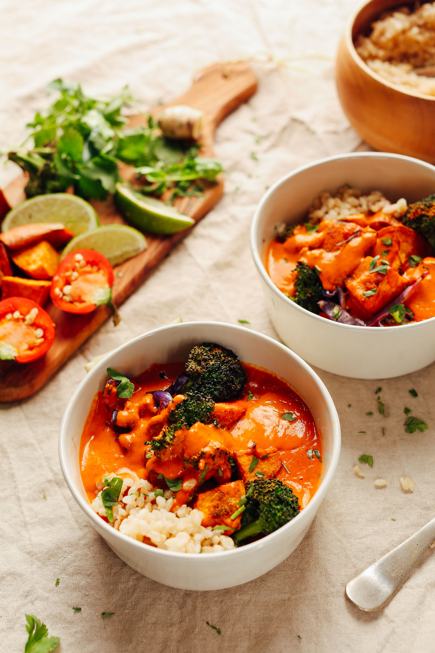 Bowls of Rich Red Curry with Roasted Vegetables alongside a cutting board with fresh limes, peppers, and herbs for serving