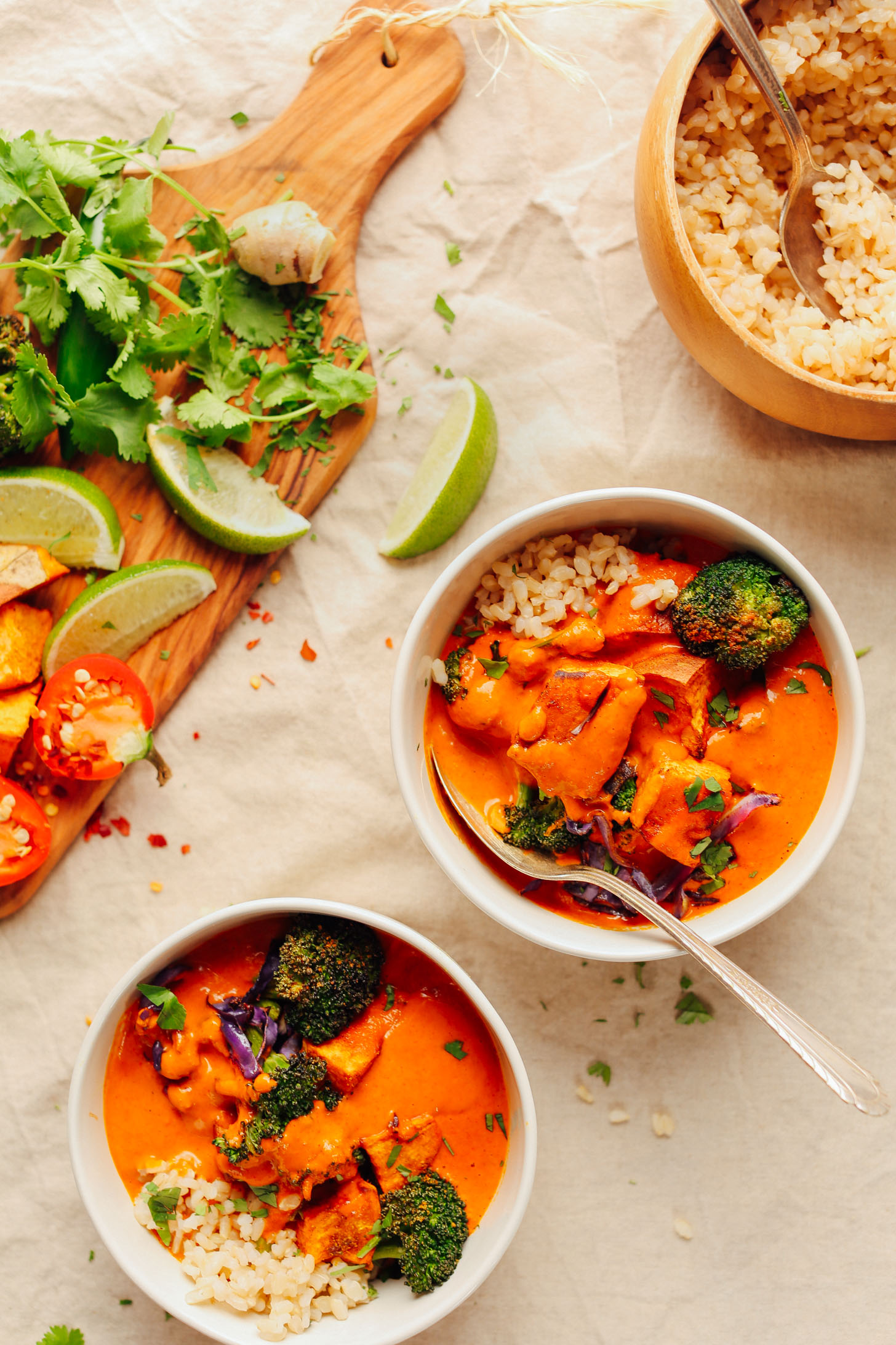 Two bowls of Rich Red Curry served with rice and fresh garnishes of lime and cilantro