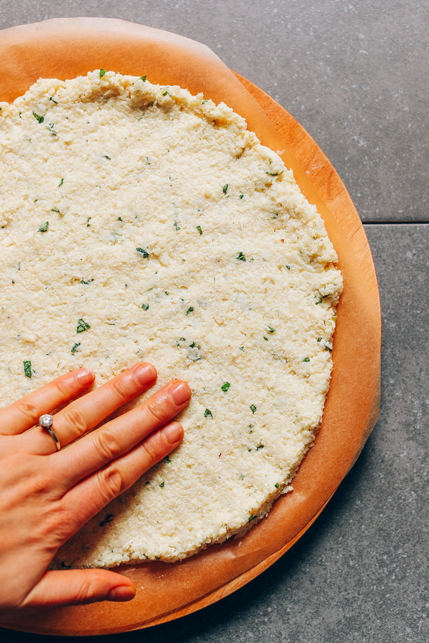Nicely flattened Gluten-Free Cauliflower Pizza Crust dough on a parchment-lined pizza tray