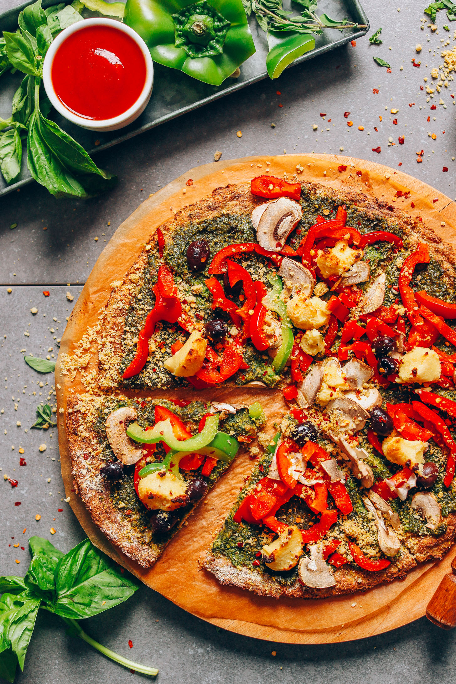 Freshly sliced, veggie-loaded pizza made with our vegan Gluten-Free Cauliflower Pizza Crust recipe
