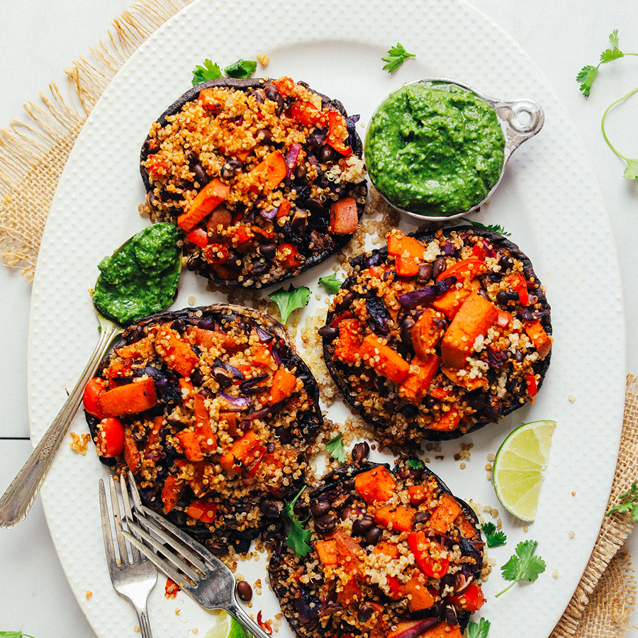 Vegetable Quinoa Stuffed Portobello Mushrooms on a platter with chimichurri sauce