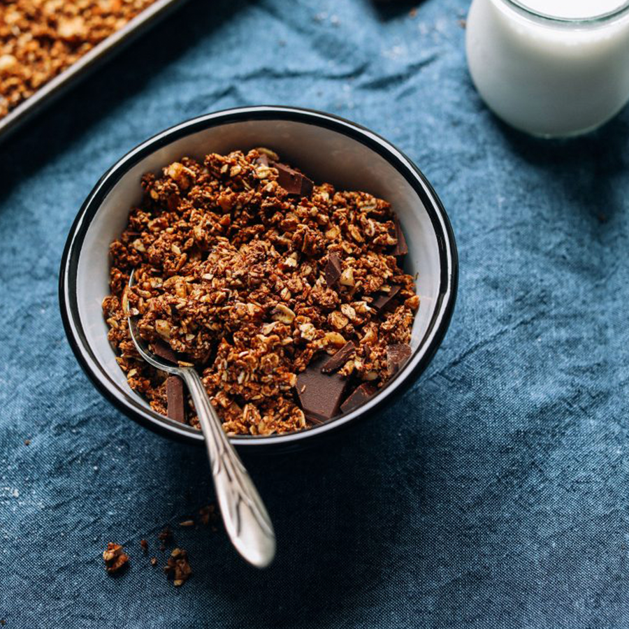 Bowl of gluten-free Dark Chocolate Sea Salt Granola with a side of dairy-free milk