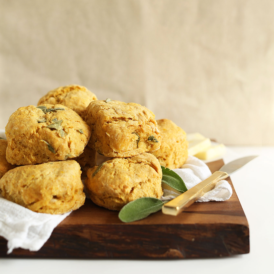 Batch of Vegan Pumpkin Sage Biscuits on a wood cutting board