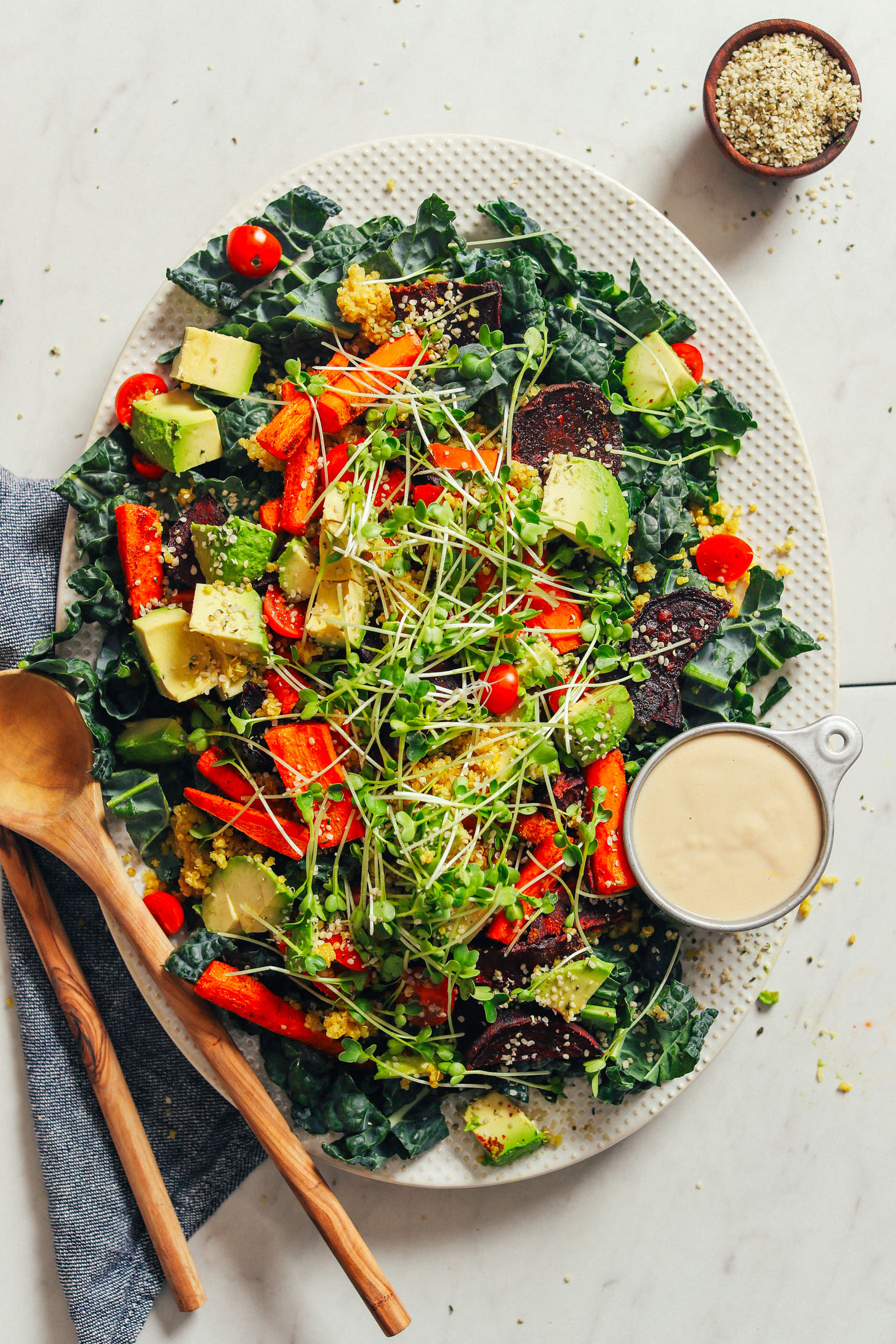 Large platter filled with vegan and gluten-free Loaded Kale Salad with sides of extra hemp seeds and tahini dressing