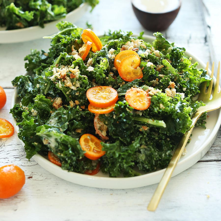Big plate of Kale Salad topped with slice kumquats