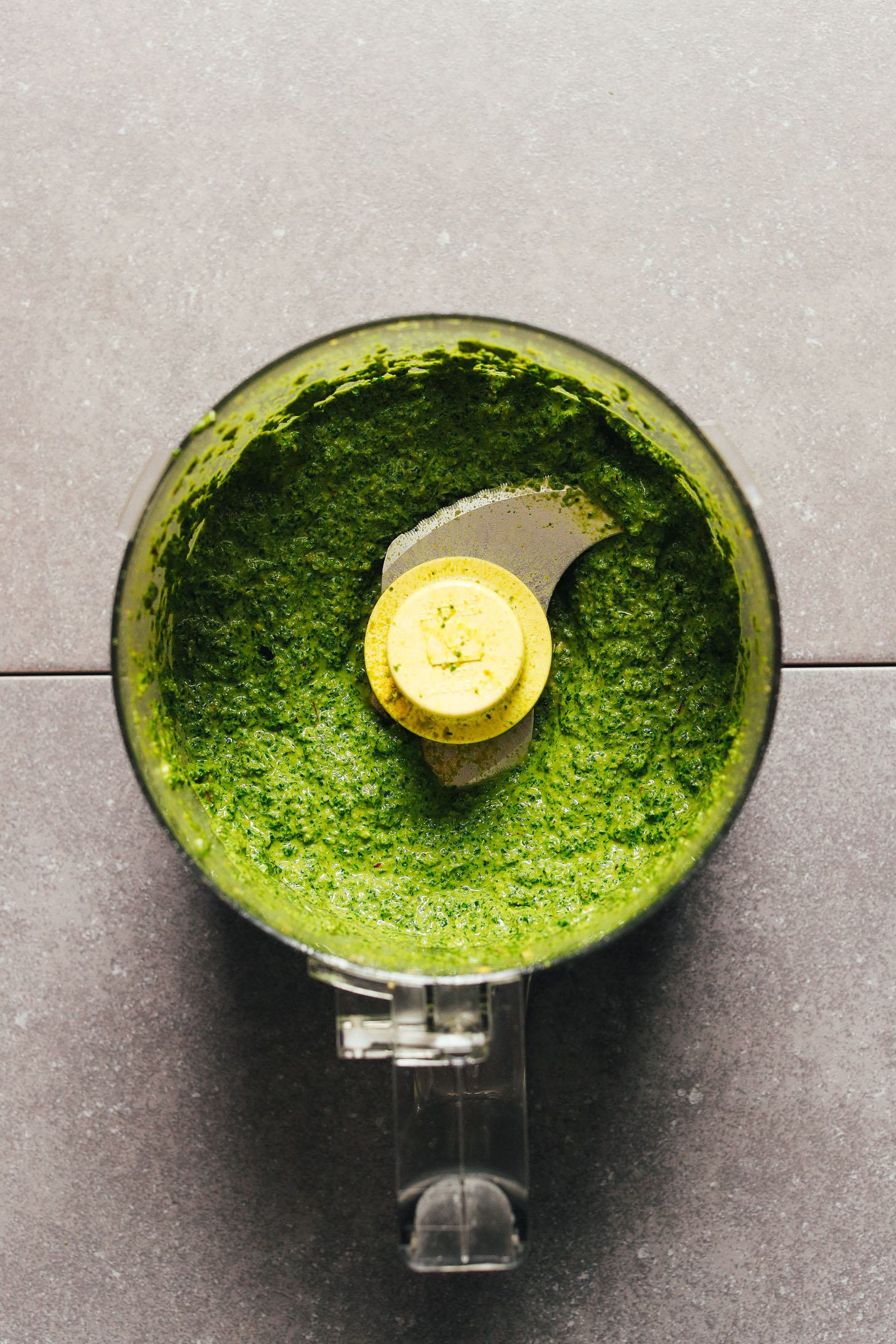 Food processor with freshly pulsed pesto made with vegan and gluten-free ingredients