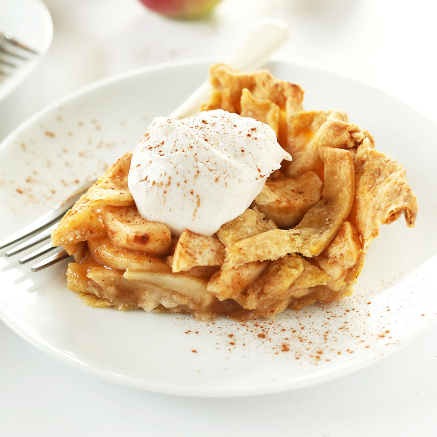 Slice of our simple and delicious Pumpkin Spiced Apple Pie topped with coconut whipped cream