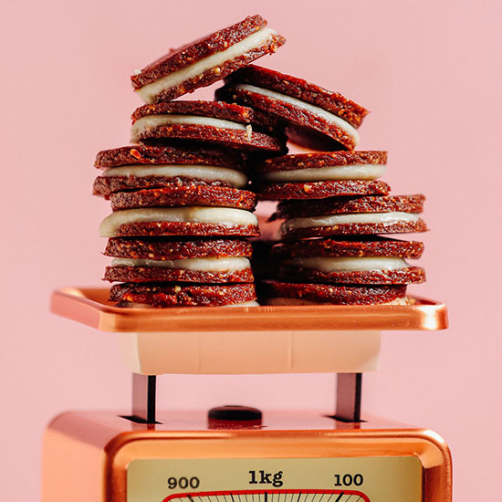 Vintage scale piled high with homemade Raw Vegan Oreos