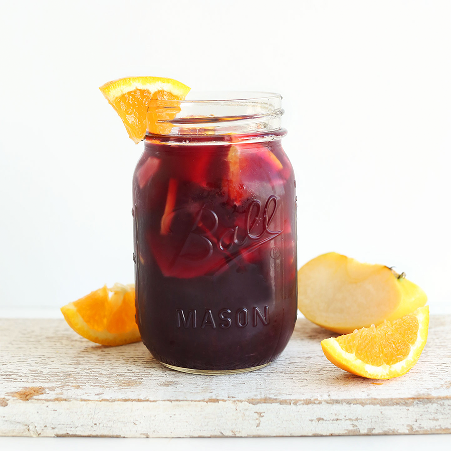 Orange and apple wedges around a jar of Traditional Red Sangria