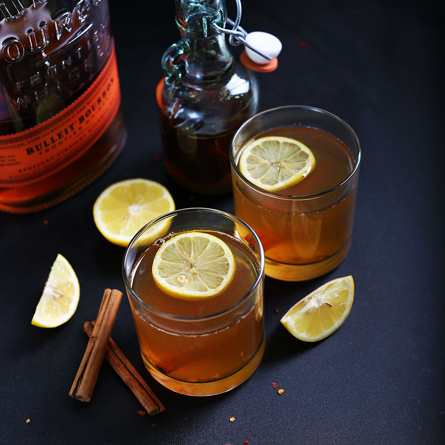 Two glasses of our Chili Cinnamon Hot Toddy recipe surrounded by ingredients used to make it