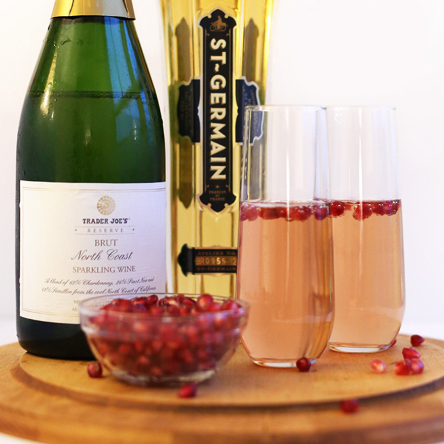 Fresh pomegranate arils, bottle of sparkling wine, bottle of St Germain and two tall glasses of St. Germain Pomegranate Spritzers