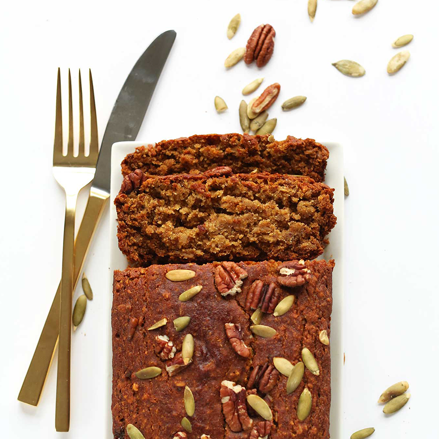 Partially sliced loaf of Vegan GF Pumpkin Bread topped with pumpkin seeds and pecans