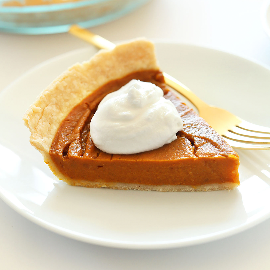 Slice of delicious Gluten-Free Vegan Pumpkin Pie topped with coconut whipped cream