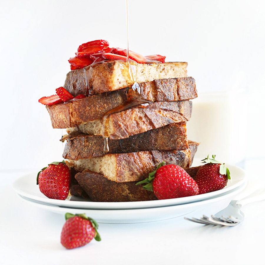 Drizzling syrup onto a plate loaded high with Vegan French Toast with Strawberries
