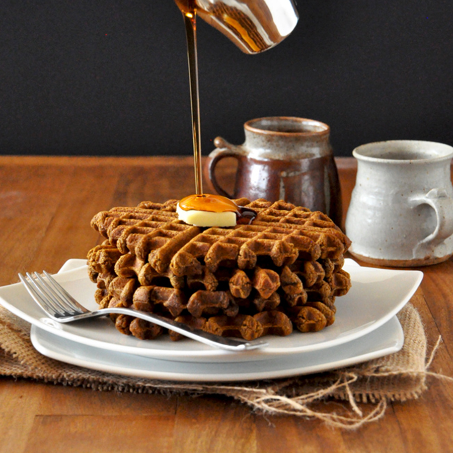 Pouring syrup onto a slab of vegan butter atop homemade Gingerbread Waffles