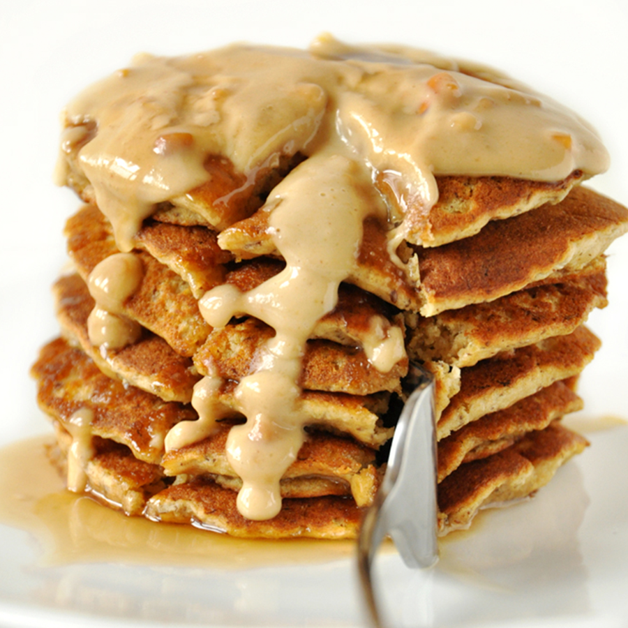 Using a fork to slice into a stack of Vegan Peanut Butter Pancakes