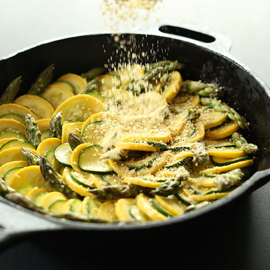 Sprinkling vegan parmesan cheese onto a skillet of our Zucchini Asparagus Gratin