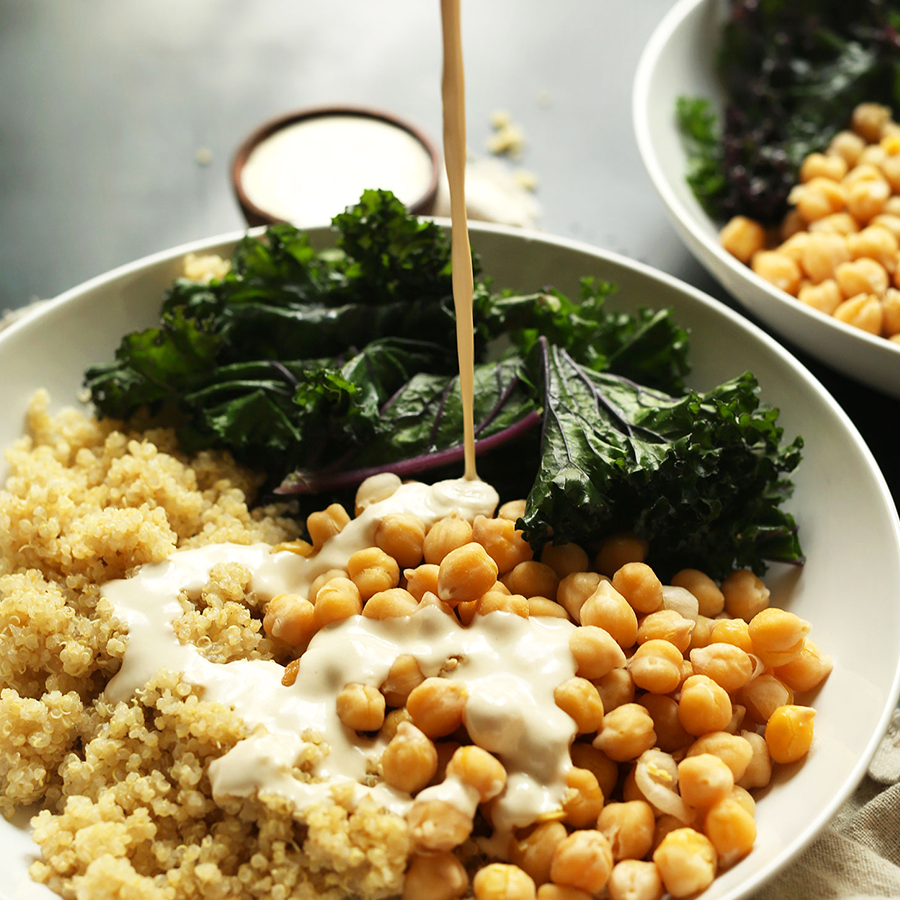 Pouring tahini sauce over chickpeas, quinoa, and kale