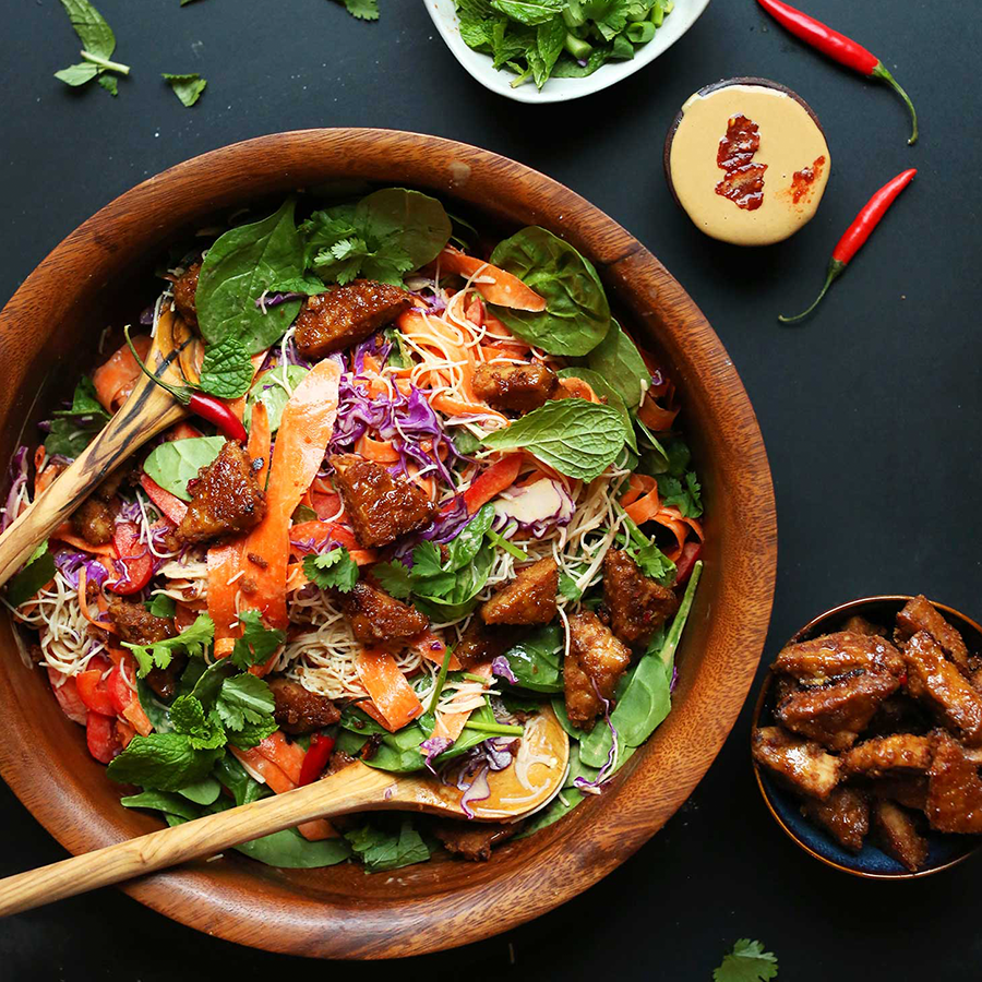 Wood bowl filled with our Blissed Out Thai Salad recipe topped with tempeh