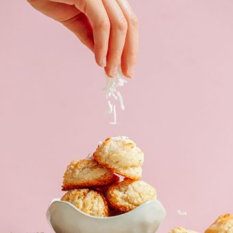 Sprinkling coconut onto a stack of our delicious Vegan Coconut Snowball Cookies