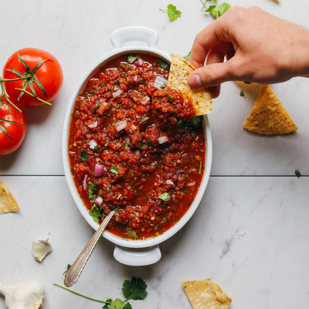 Dipping a tortilla chip into a dish of Perfect Red Salsa for a homemade Super Bowl Snack
