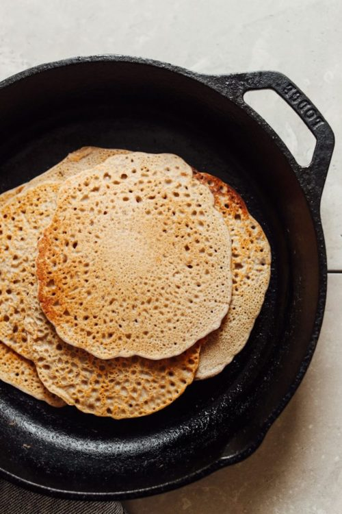 An overhead shot of buckwheat vegan crepes in a cast iron skillet