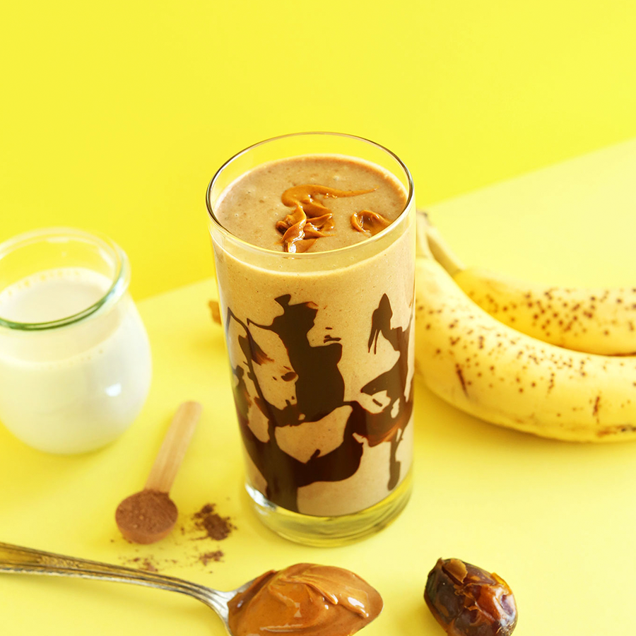 Tall glass of our delicious Vegan Peanut Butter Banana Milkshake recipe beside ingredients to make it