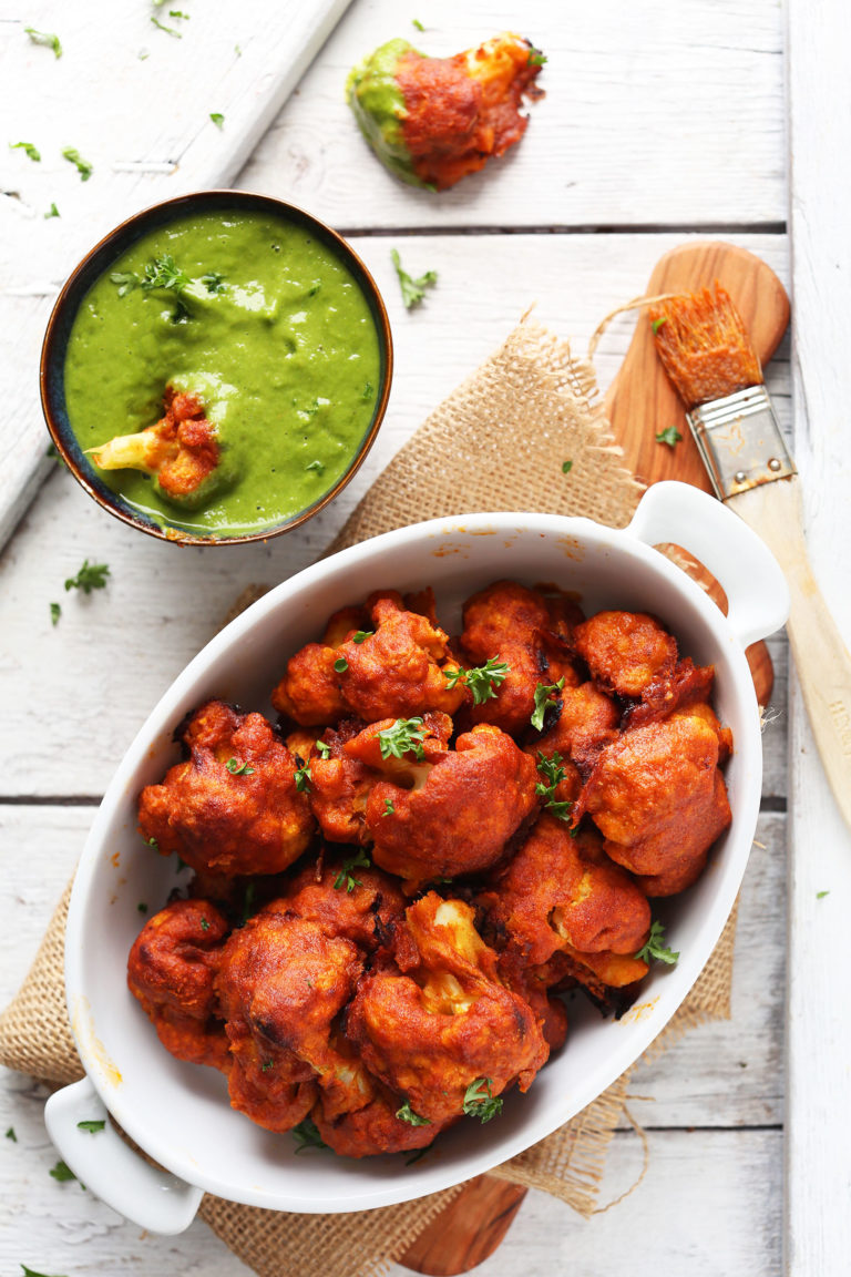 Red Curry Cauliflower in a dish and dipped in green chutney for a Plant-Based Super Bowl Snack