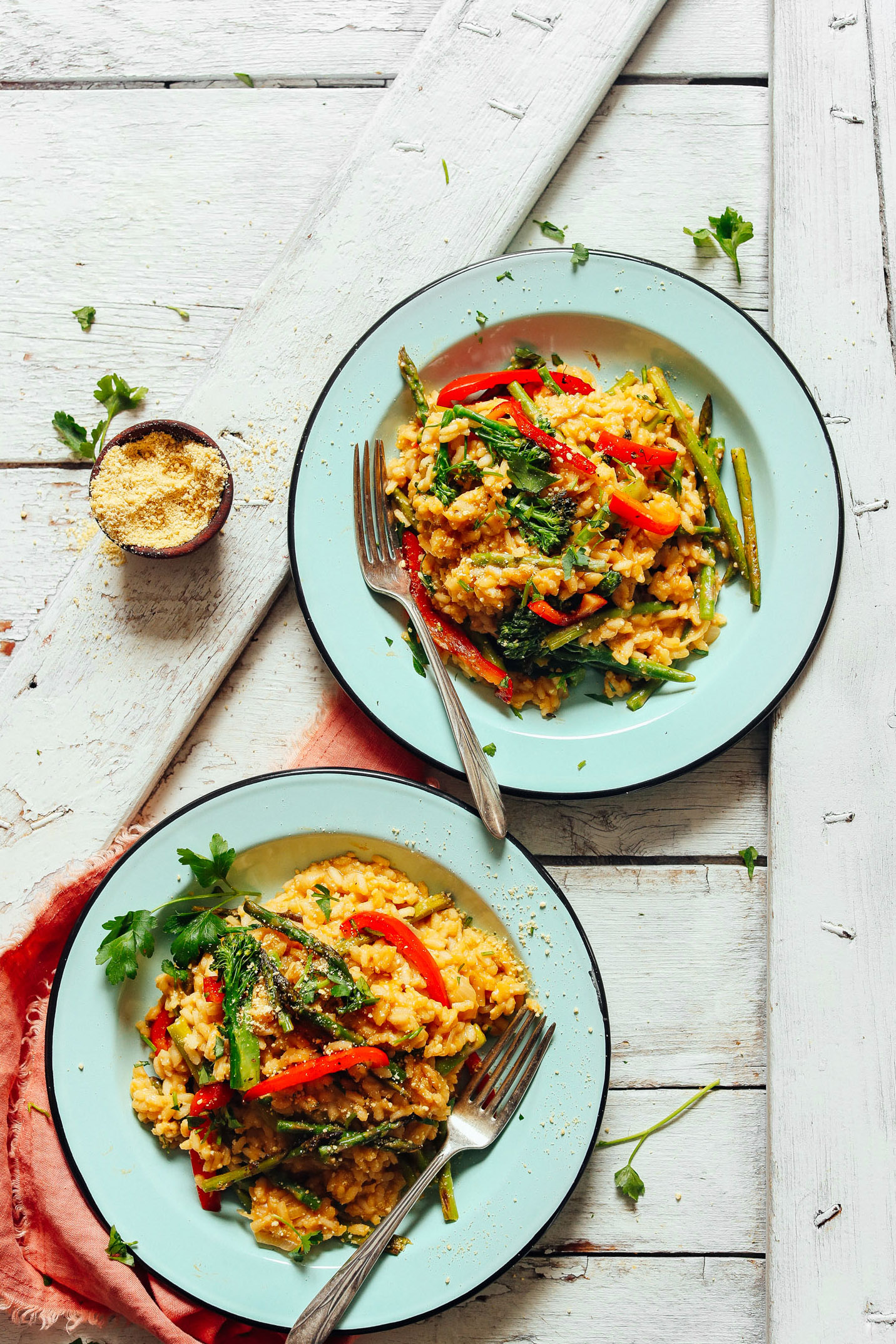 Two hearty servings of Creamy Vegetable Risotto in dinner bowls with a side of vegan parmesan