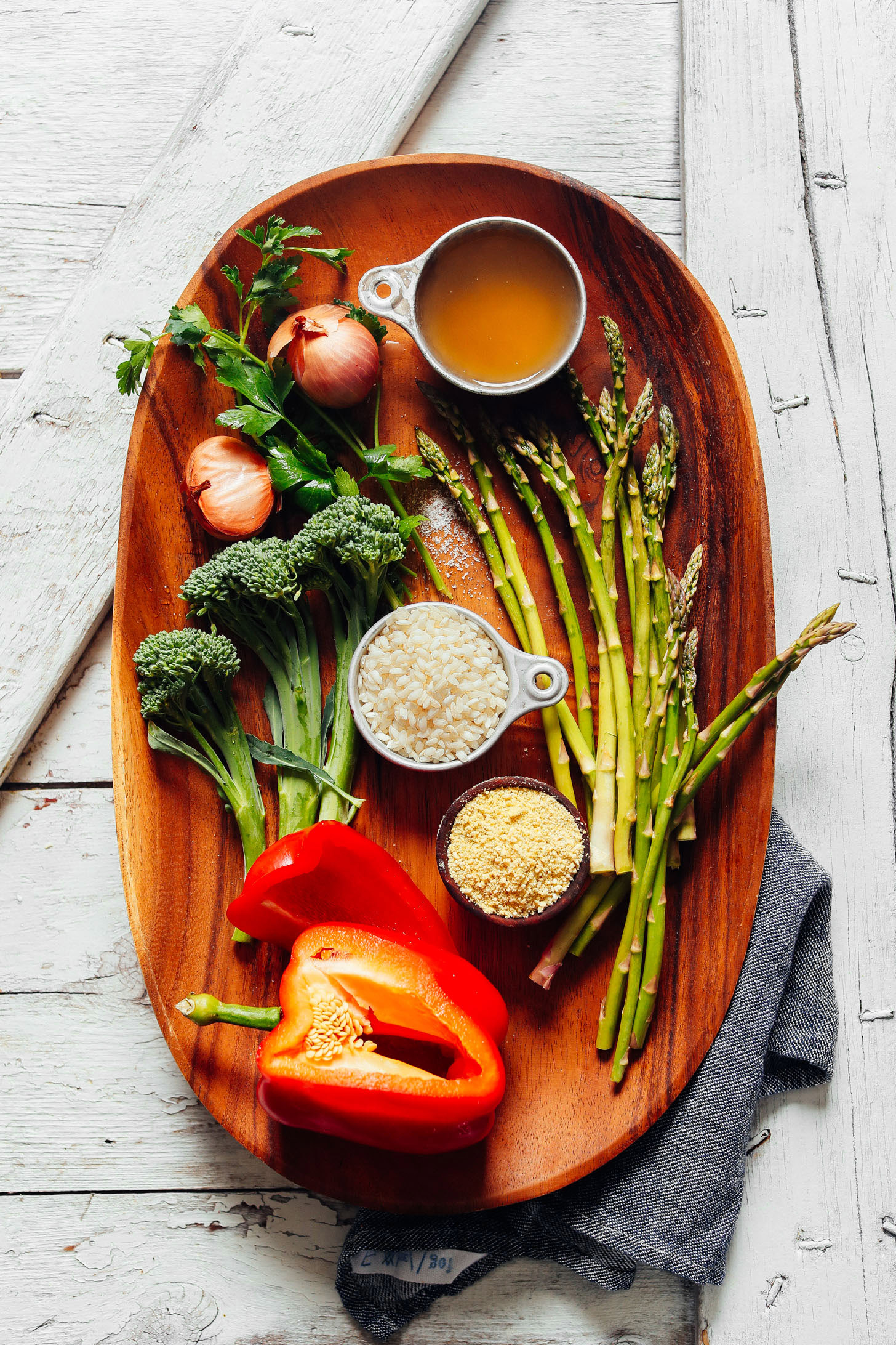 Wood serving platter displaying broccolini, shallots, parsley, red bell pepper, arborio rice, asparagus, vegetable broth, and vegan parmesan for making Creamy Vegetable Risotto