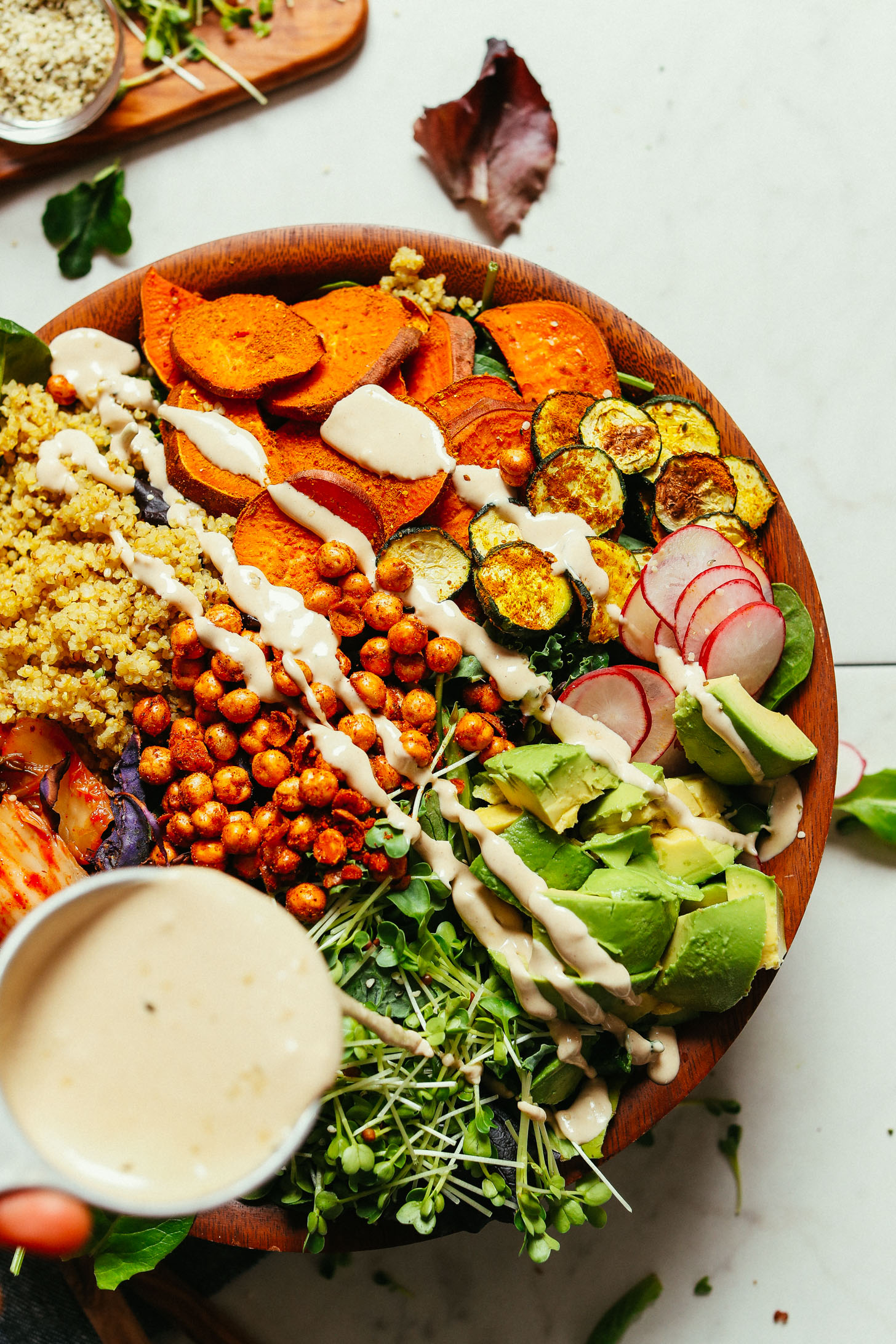 Drizzling Savory Tahini Dressing over our healthy, colorful Abundance Green Salad
