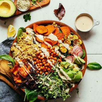 A large salad bowl filled with our Abundance Green Salad with Savory Tahini Dressing- the perfect gluten-free vegan meal
