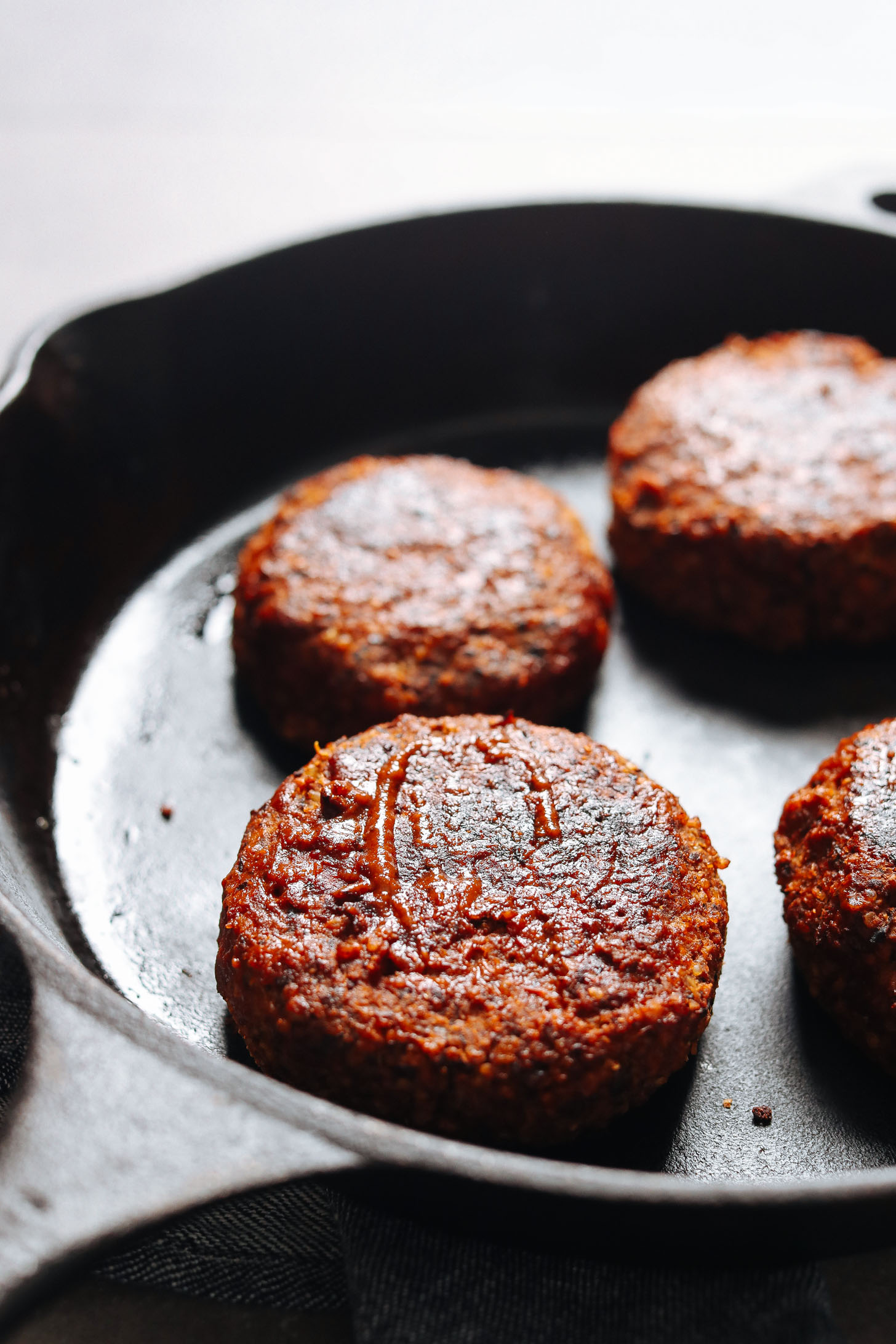 Gluten-free and vegan BBQ Black Bean Burger patties cooking in a skillet